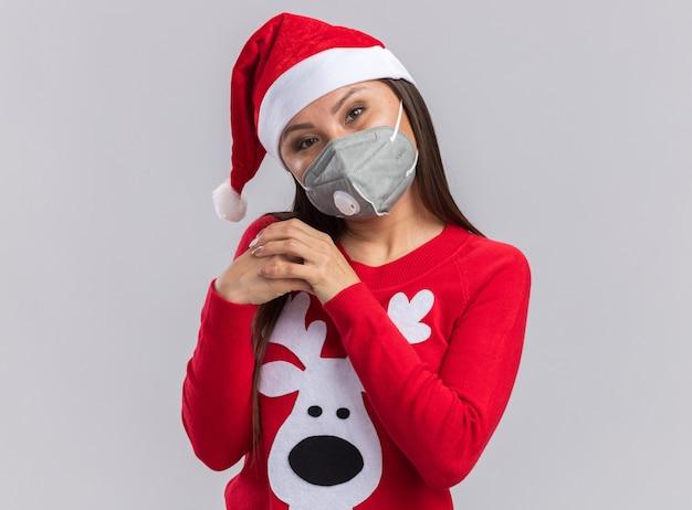 Zadowolona przechylająca się głowa młoda azjatycka dziewczyna w świątecznym kapeluszu ze swetrem i maską medyczną trzymającą się razem za ręce na białym tle