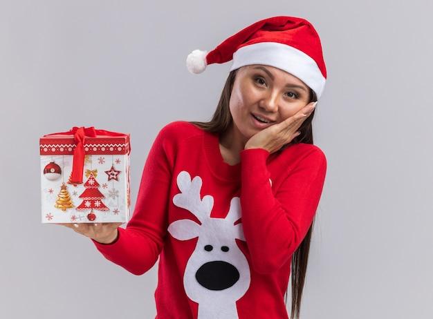 Zadowolona przechylająca się głowa młoda azjatycka dziewczyna w świątecznym kapeluszu ze swetrem, trzymająca pudełko, kładąc rękę na policzku na białym tle