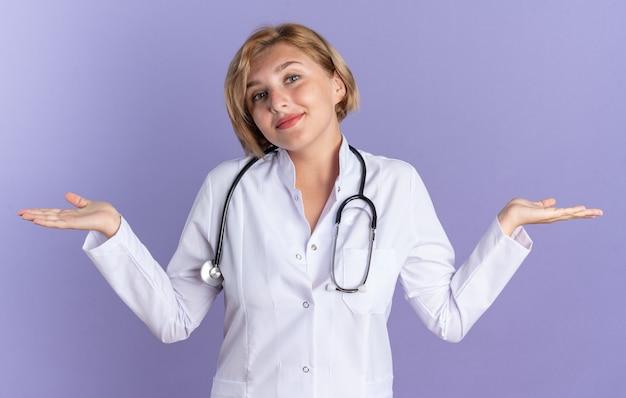 Zadowolona przechylająca się głowa młoda lekarka ubrana w szatę medyczną ze stetoskopem rozkładającym ręce izolowane na niebieskiej ścianie