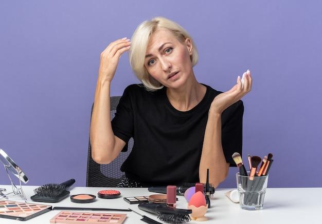 Zadowolona przechylająca się głowa młoda piękna dziewczyna siedzi przy stole z narzędziami do makijażu, trzymając krem do włosów na niebieskiej ścianie