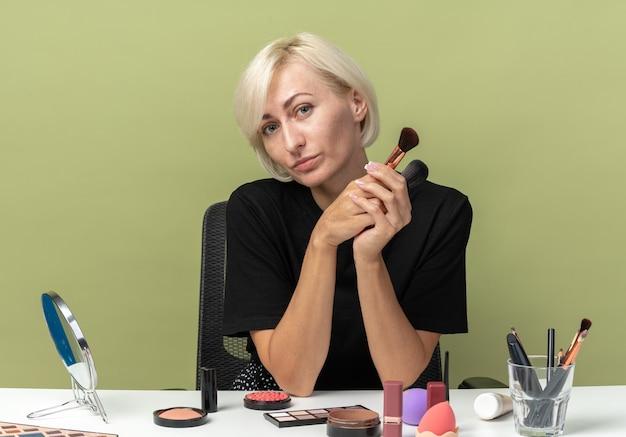 Zadowolona przechylająca się głowa młoda piękna dziewczyna siedzi przy stole z narzędziami do makijażu, trzymając pędzle do pudru izolowane na oliwkowozielonej ścianie