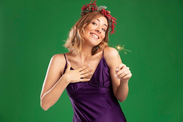 Zadowolona, przechylająca się głowa młoda piękna dziewczyna ubrana w fioletową sukienkę z wieńcem, trzymająca zimne ognie, kładąc rękę na sobie na białym tle na zielonym tle