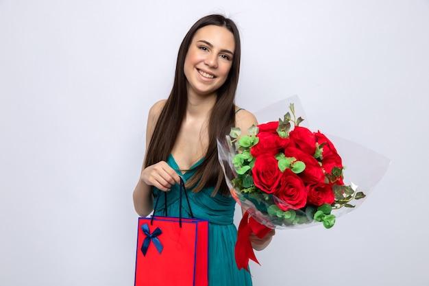 Zadowolona przechylająca się głowa piękna młoda dziewczyna trzyma bukiet z torbą na prezent