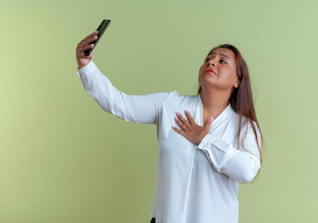 Zadowolona, przypadkowa kaukaska kobieta w średnim wieku robi selfie i kładzie rękę na ramieniu