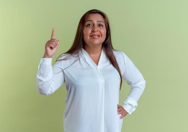 Zadowolona, przypadkowa kaukaska kobieta w średnim wieku wskazuje w górę i kładzie rękę na biodrze