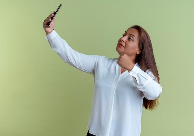Zadowolona przypadkowa kaukaski kobieta w średnim wieku bierze selfie i trzyma pięść