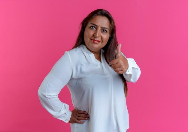 Zadowolona przypadkowa kaukaski kobieta w średnim wieku kładąca rękę na biodrze jej kciuk w górę