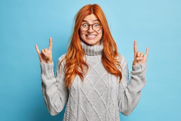Zadowolona radosna rudowłosa kobieta w okularach pokazuje rock n rollowy znak ręką gest diabła rogów, szeroko uśmiechnięty, pokazuje białe zęby w zimowym swetrze.
