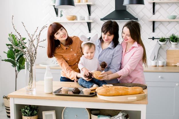 Zadowolona rodzina z babcią, dwiema córkami i małą córeczką, ciesząc się rozrywką na wielkanoc i jedząc babeczki. mała dziewczynka ma uszy królika na głowie.