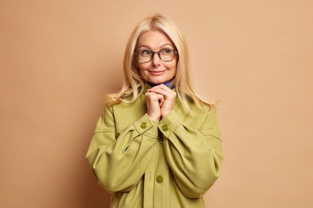 Zadowolona, rozmarzona starsza kobieta trzyma ręce ściśnięte pod brodą, rozważa pomysł, nosi zieloną kurtkę z okularami optycznymi.