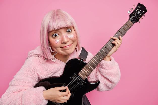 Zadowolona różowowłosa kobieta gra na gitarze elektrycznej, wykonuje ulubiony gatunek muzyki, ma twarz ozdobioną brokatem ubraną w płaszcz