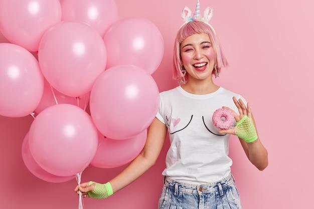 Zadowolona różowowłosa kobieta trzyma pęk balonów smaczny przeszklony pączek uśmiecha się z radością lubi spędzać wolny czas na imprezie nosi luźną koszulkę dżinsy sportowe rękawiczki