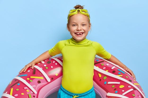 Zadowolona ruda dziewczyna pozuje w swoim stroju na basenie
