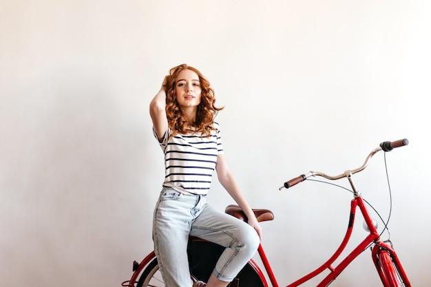 Zadowolona ruda kobieta w pasiastej koszulce siedzi na rowerze. jocund modelka bawi się z kręconymi włosami.