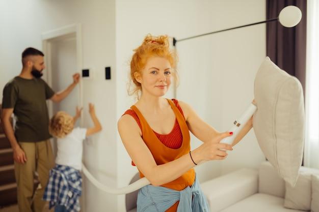 Zadowolona rudowłosa kobieta trzyma odkurzacz