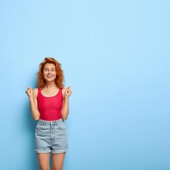 Zadowolona rudowłosa modelka zaciska pięści, oczekuje czegoś dobrego, uśmiecha się radośnie, nosi czerwoną kamizelkę i dżinsowe szorty