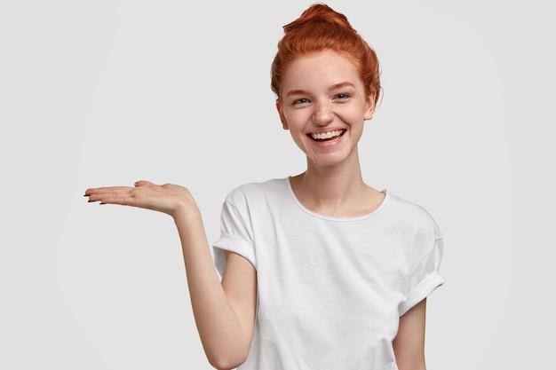 Zadowolona śliczna europejka z rudymi włosami trzyma miejsce na kopię, trzyma dłoń uniesioną, reklamuje coś na białej ścianie, ma figlarny wyraz twarzy