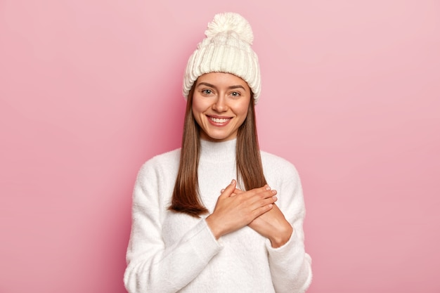 Zadowolona śliczna kobieta o prostych włosach, dostaje ciepłe słowa od chłopaka, robi wdzięczny gest, nosi wygodny biały sweter i kapelusz, odizolowana na różowej ścianie