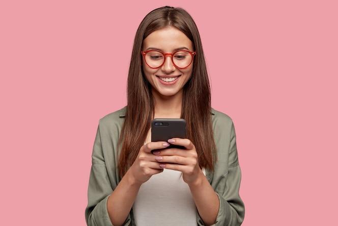 Zadowolona śliczna kobieta trzyma nowoczesny telefon komórkowy