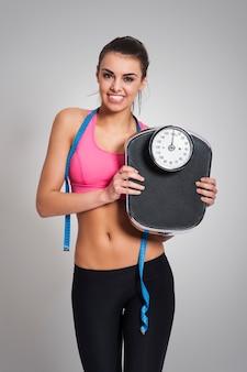 Zadowolona, sprawna kobieta z wagą