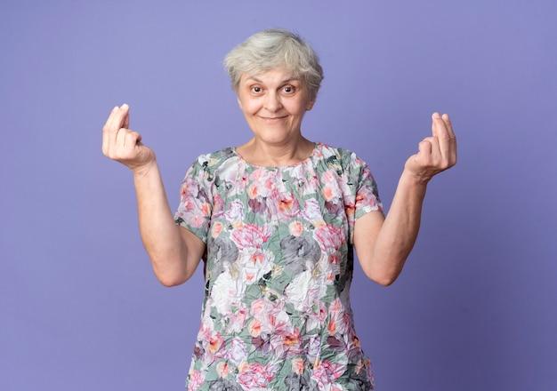 Zadowolona starsza kobieta gestów pieniądze ręka znak dwiema rękami odizolowanymi na fioletowej ścianie