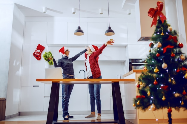 Zadowolona starsza kobieta i jej ciężarna córka świętują nowy rok. obie mają na głowie czapki mikołaja i stoją w kuchni. sylwester.