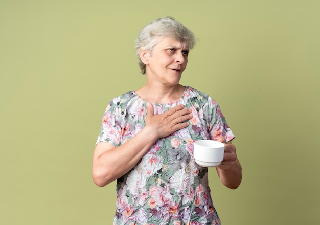 Zadowolona starsza kobieta kładzie rękę na piersi i trzyma kubek patrząc z boku na tle oliwkowej ściany