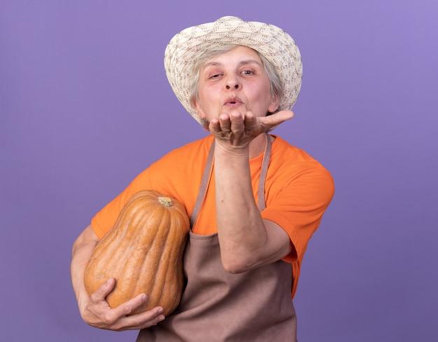 Zadowolona starsza kobieta ogrodniczka w kapeluszu ogrodniczym trzymająca dynię i wysyłająca pocałunek ręką patrzącą na kamerę