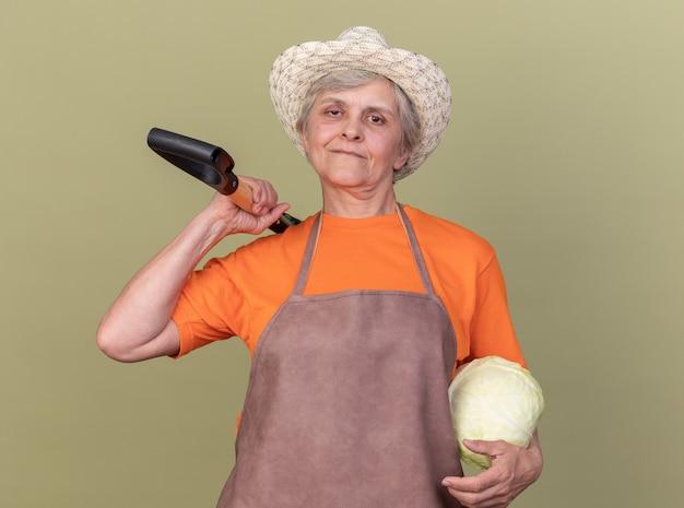 Zadowolona starsza kobieta ogrodniczka w kapeluszu ogrodniczym trzymająca kapustę i łopatę na ramieniu