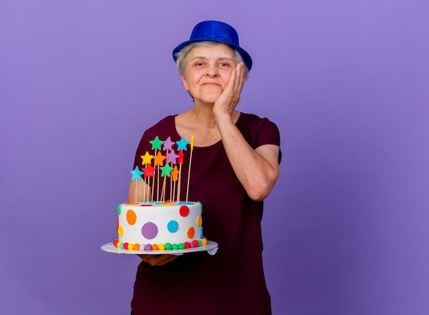 Zadowolona starsza kobieta w kapeluszu imprezowym kładzie rękę na twarzy i trzyma tort urodzinowy na fioletowej ścianie