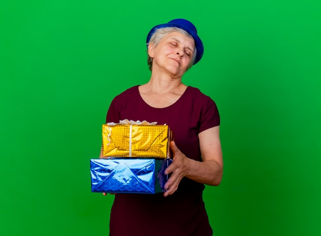 Zadowolona starsza kobieta w kapeluszu imprezowym z zamkniętymi oczami trzyma pudełka na prezenty na zielono