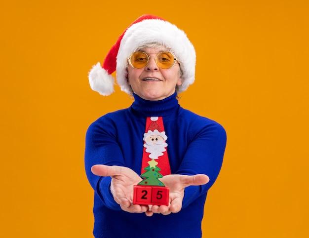Zadowolona starsza kobieta w okularach przeciwsłonecznych z czapką świętego mikołaja i krawatem świętego mikołaja, trzymająca ornament choinkowy odizolowana na pomarańczowej ścianie z kopią przestrzeni