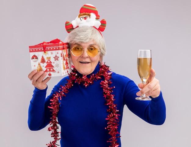 Zadowolona starsza kobieta w okularach przeciwsłonecznych z opaską świętego mikołaja i girlandą na szyi trzyma kieliszek szampana i świąteczne pudełko na białym tle na białej ścianie z miejscem na kopię