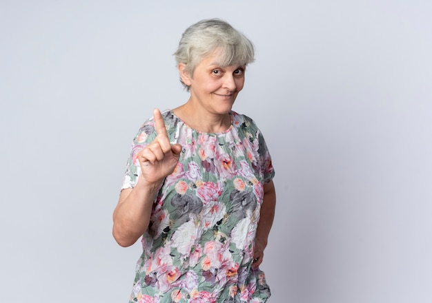 Zadowolona starsza kobieta wskazuje na białym tle na białej ścianie
