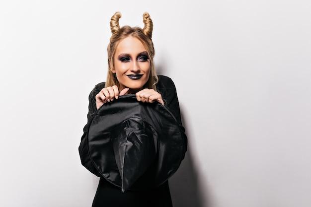 Zadowolona stylowa kobieta w czarnym stroju świętuje halloween. urocza dziewczyna w stroju czarownicy przygotowuje się do imprezy.