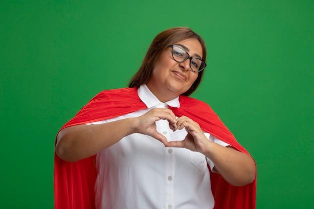 Zadowolona superbohaterka w średnim wieku w okularach pokazująca gest serca na zielono