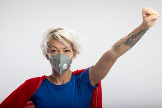 Zadowolona superwoman w czerwonej pelerynie ubrana w statywy medyczne z maską z podniesioną pięścią na białej ścianie