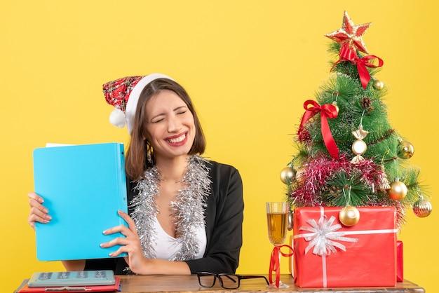Zadowolona szczęśliwa czarująca pani w garniturze z czapką świętego mikołaja i dekoracjami noworocznymi trzyma dokument w biurze na żółto na białym tle