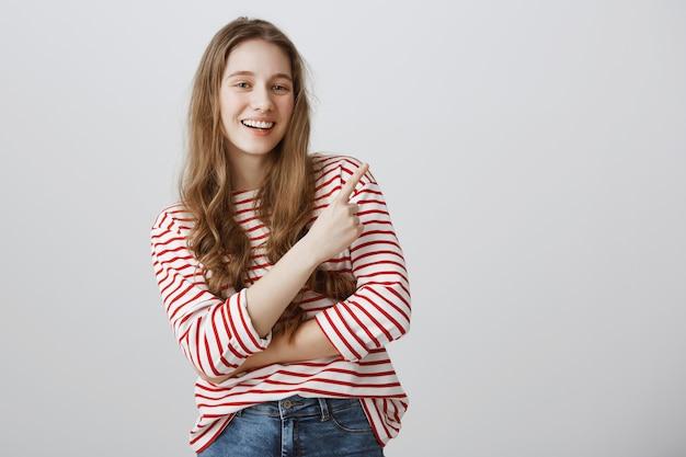 Zadowolona szczęśliwa dziewczyna uśmiecha się, wskazując prawy górny róg