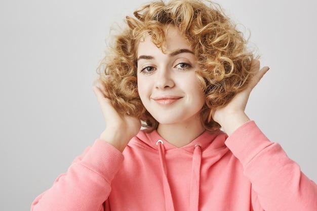 Zadowolona szczęśliwa młoda kobieta zadowolona z nowej kręconej fryzury
