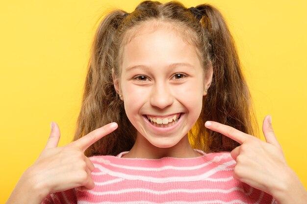Zadowolona szczęśliwa radosna dziewczyna wskazując na jej uśmiech. stomatologia dziecięca i zdrowe zęby.