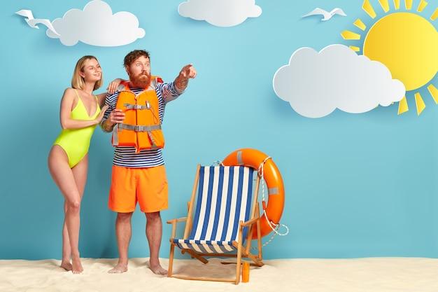Zadowolona szczupła kobieta z fryzurą na grzywce, nosi jasnozielony kostium kąpielowy, opiera się na ramieniu kochanka, który ma zszokowany wyraz twarzy