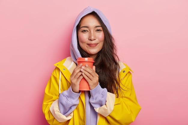 Zadowolona tysiącletnia dziewczyna o azjatyckim wyglądzie, bez makijażu, ubrana w fioletową bluzę i płaszcz przeciwdeszczowy, trzyma termos z gorącym napojem, próbuje się ogrzać przy herbacie