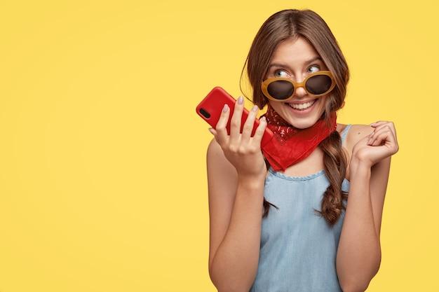 Zadowolona, urocza kobieta nosi modne okulary przeciwsłoneczne, trzyma telefon komórkowy, słucha przyjemnej melodii, korzysta z szybkiego internetu, czeka na ważny telefon, odizolowana na żółtej ścianie z miejscem na kopię