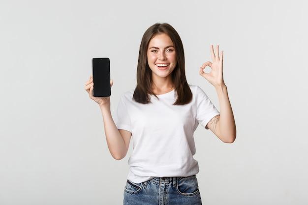Zadowolona uśmiechnięta brunetka dziewczyna pokazuje ekran smartfona i pokazuje dobry gest z aprobatą.
