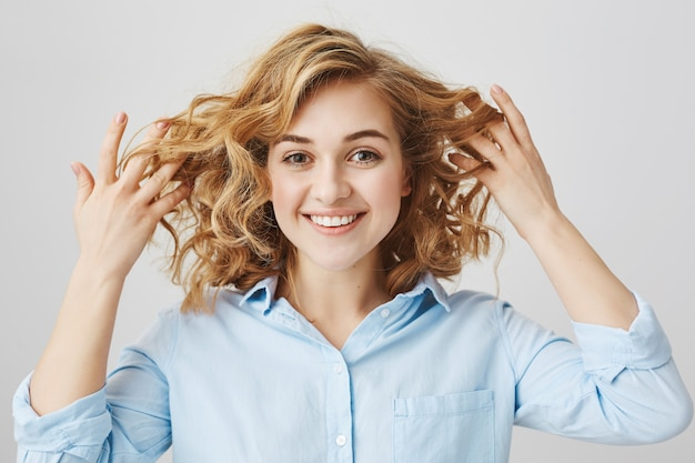 Zadowolona uśmiechnięta dziewczyna pokazuje kręcone włosy po salon fryzjerski