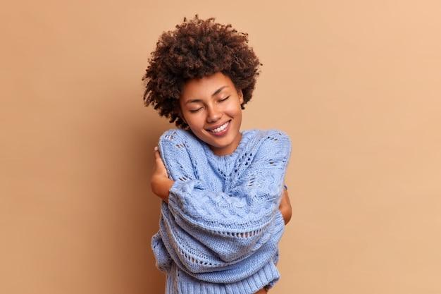Zadowolona uśmiechnięta kobieta o krzaczastych, kręconych włosach obejmuje się z miłością rozkoszując się miękkością nowego swetra czuje się komfortowo i zachwycona zamyka z satysfakcją oczy odizolowane na beżowej ścianie