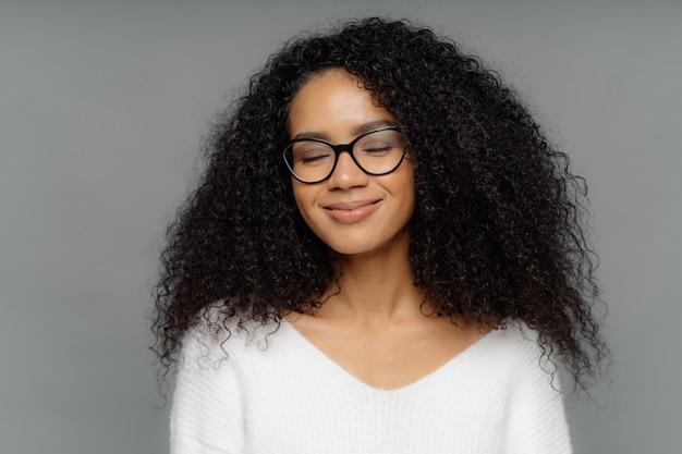 Zadowolona uśmiechnięta kobieta o krzaczastych, ostrych włosach, trzyma oczy zamknięte, uśmiecha się delikatnie, nosi okulary optyczne
