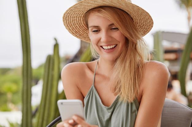 Zadowolona, uśmiechnięta młoda kobieta o wesołym wyrazie twarzy nosi letnie ubrania, chętnie otrzymuje wiadomość lub czyta pozytywne wiadomości online na smartfonie, podłączonym do bezprzewodowego internetu w kawiarni na świeżym powietrzu