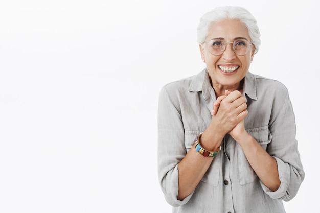 Zadowolona, uśmiechnięta starsza kobieta składa ręce razem i wygląda na zachwyconą